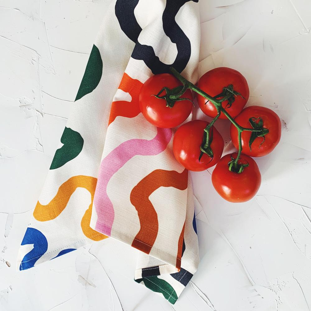 This image shows a cotton-linen kitchen towel in the Paths print, laid next to market fresh tomatoes. Thick curving lines fill the design in saturated bright colours; yellow, blue, dark green, dark blue, caramel and pink on a white background.