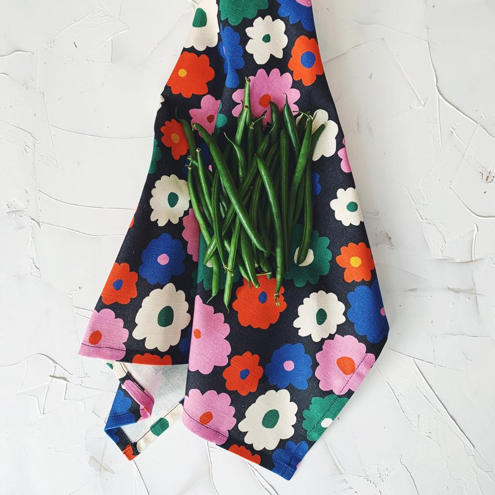 This image shows a cotton-linen kitchen towel in the Power print, laid next to market fresh green beans. Small to medium flowers fill the design in saturated bright colours; red, blue, white, green and pink on a black background.