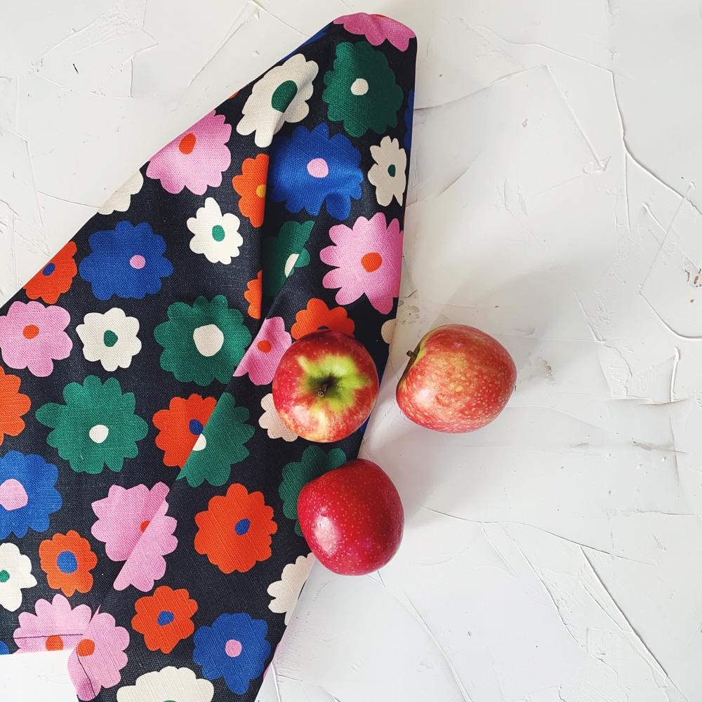 This image shows a cotton-linen kitchen towel in the Power print, laid next to market fresh apples. Small to medium flowers fill the design in saturated bright colours; red, blue, white, green and pink on a black background.
