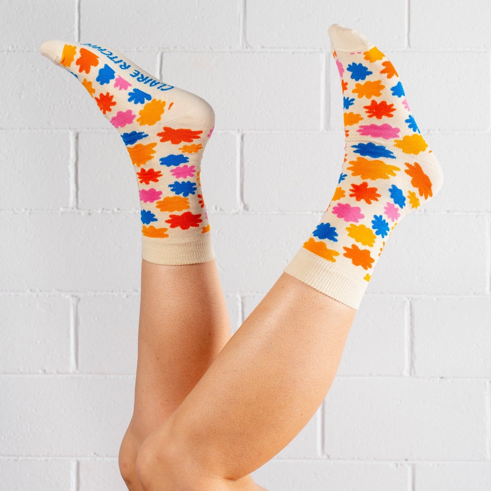 A pair of cotton-blend socks designed by Claire Ritchie. A model wears a cream sock, dotted with flowers in turmeric, orange, pink and blue. The words Claire Ritchie are printed on the sole of the foot in blue.