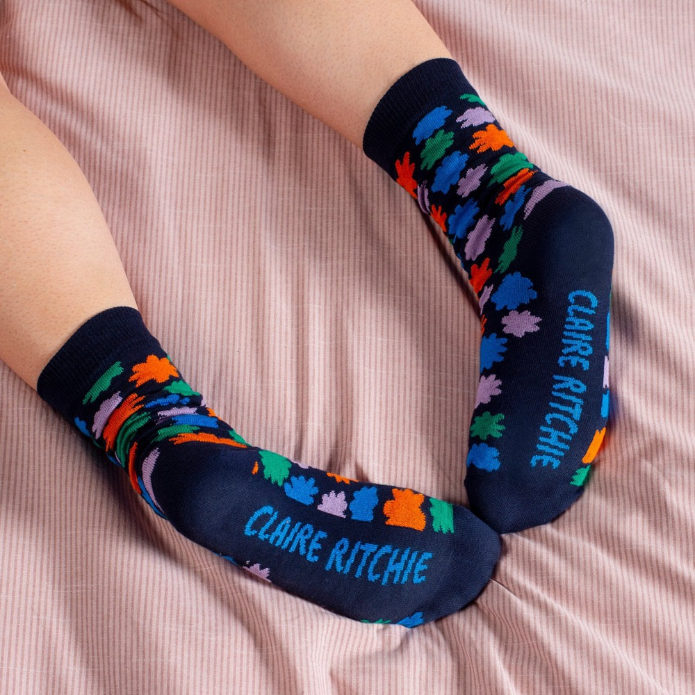 A pair of cotton-blend socks designed by Claire Ritchie. A model wears a navy sock, dotted with flowers in red, violet, forrest green and blue. The words Claire Ritchie are printed on the sole of the foot.