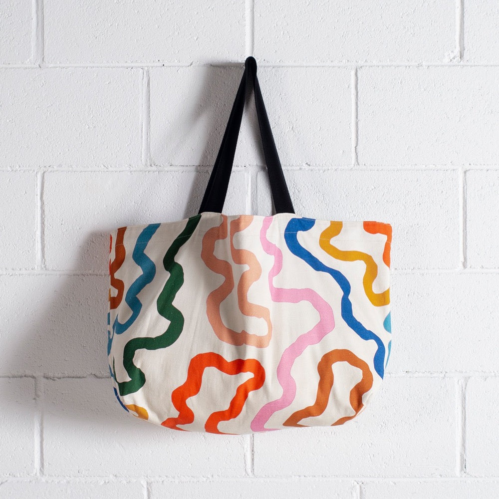 Image shows a large reversible bag in the Paths print. The bag has a black shoulder strap, and the cream body sports thick curving lines in peach, pink, caramel, orange, yellow, sky blue and dark blue.