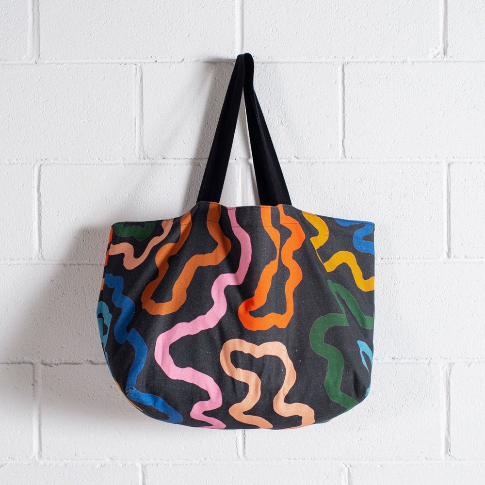 Image shows a large reversible bag in the Ways print. The bag has a black shoulder strap, and the black print sports thick curving lines in peach, pink, caramel, orange, yellow, sky blue and dark blue.
