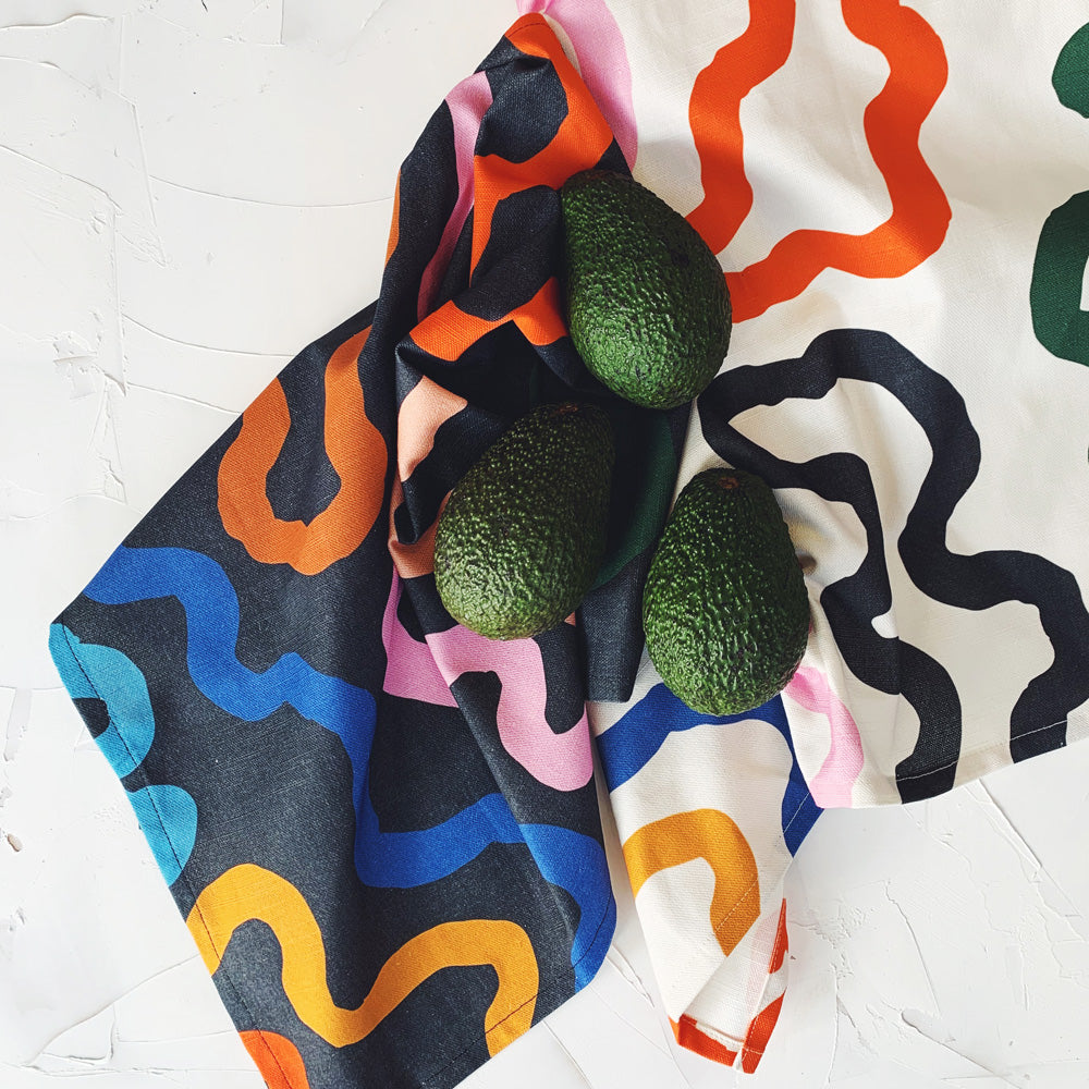 This image shows a cotton-linen kitchen towel in the Ways print (left), and the Paths print (right). Thick curving lines fill the design in saturated bright colours; orange, blue, peach, yellow, dark green, light blue, caramel and pink on a black background. Pictured with market fresh avocados.