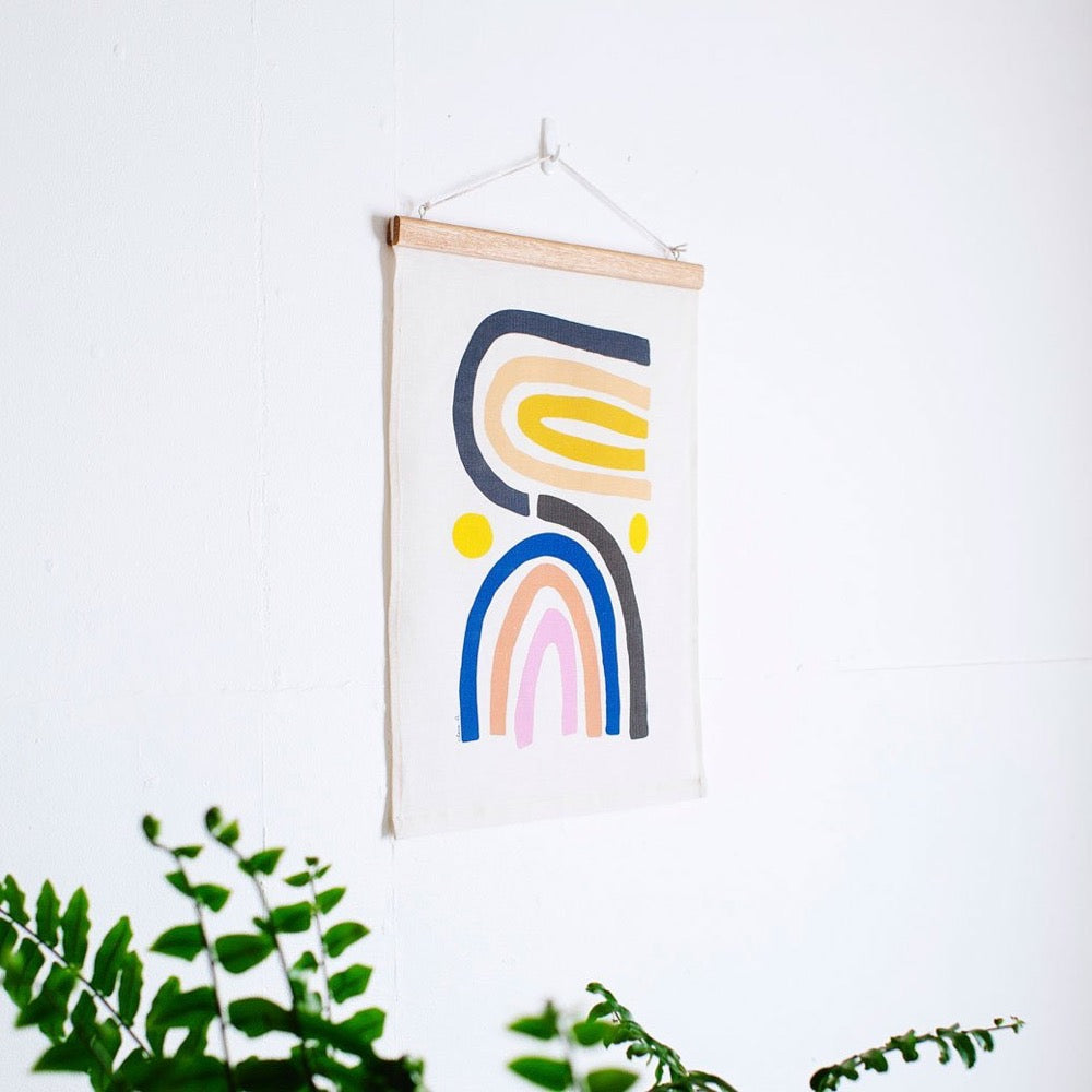 100% Linen Wall Hanging with original design by Claire Ritchie. Two multi-colour rainbows sit side by side with a yellow orb by each side. The hanging sits on a white wall with a green house plant in the bottom left of the image.
