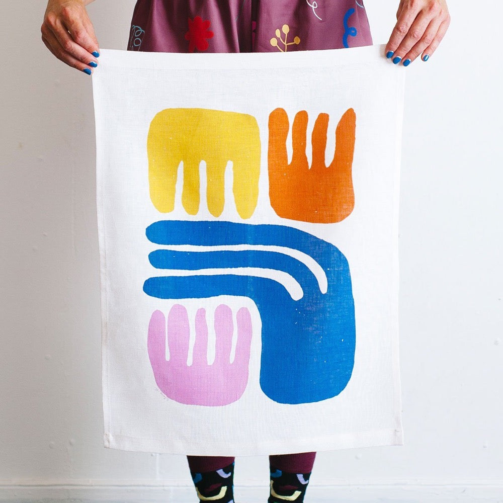 100% Linen Wall Hanging with original design by Claire Ritchie. Grouped together are four abstract comb shapes in yellow, orange, mid-blue and light pink.