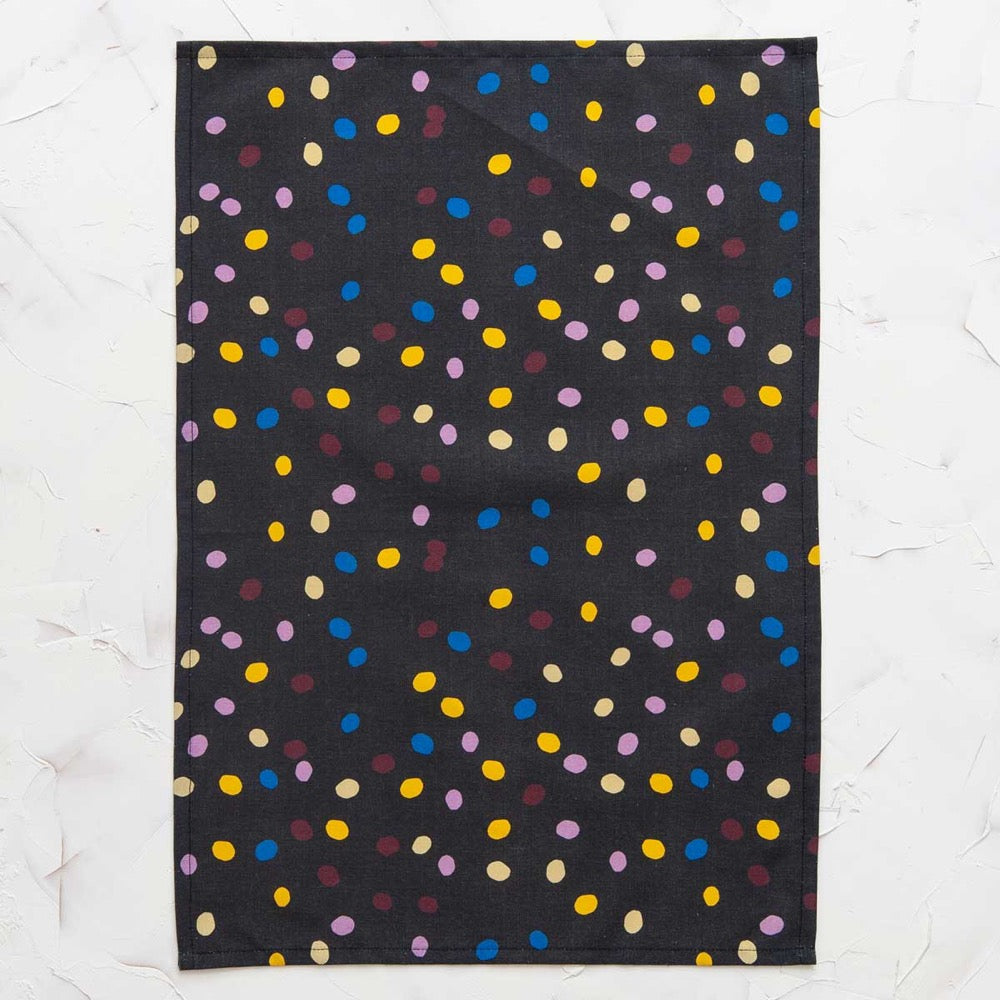 This image shows a cotton-linen kitchen towel in the Spot Speck print, laid flat. Small irregular polka dots fill the design in saturated bright colours; maroon, blue, light yellow, yellow and pink on a black background.