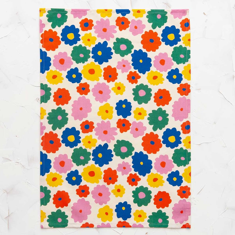 This image shows a cotton-linen kitchen towel in the Flower print, laid flat. Small to medium flowers fill the design in saturated bright colours; red, blue, yellow, green and pink.