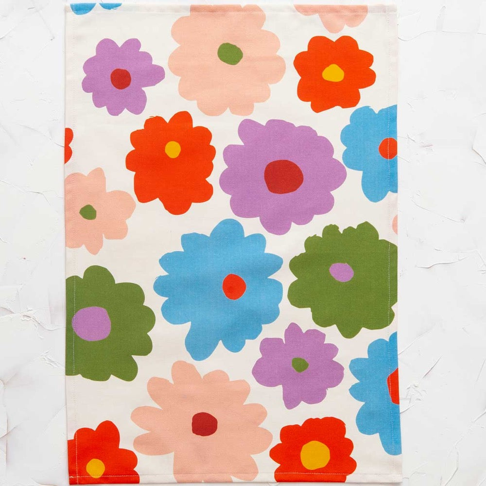 This image shows a cotton-linen kitchen towel in the Bloom print, laid flat. Large flowers fill the design in sky blue, red, violet, pink, golden yellow and olive green.