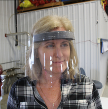 "Load image into Gallery viewer, We are making vinyl face shields out of our office in Belmont, Ontario. We have tons in stock and are able to accommodate any order sizes.  Price: $12.95 each or $10.95 each on minimum order of 50 (discount automatically applied at checkout).  Product Details: Shield - Clear Vinyl Forehead Cushion - Foam Strap - Adjustable Velcro   Dimensions:  12"" W, 8"" H (SMALL) 15.5"" W, 9"" H (LARGE)"