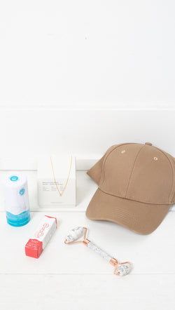 Van De Vort Stay Home Kit With a Beige Baseball Cap, Floral Oil Perfume Roll-On, Gold Dipped Teardrop Necklace, White Marble Face Roller, Coconut Deodorant, and Coconut Lip Gloss