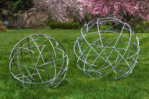 An image of large and small Nest Zinc Spheres sitting on grass.
