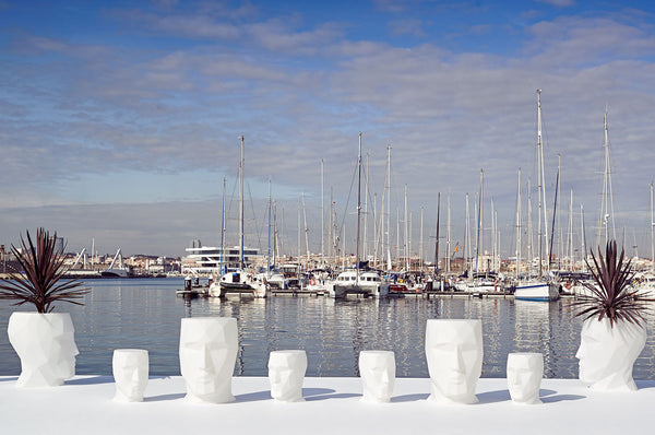 An image of the Adan Face modern planters from Creative Living on a ledge overlooking the ocean.