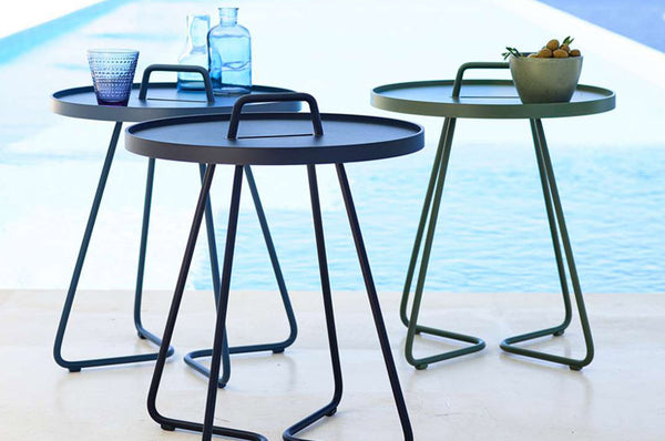 An image of three On The Move Tables from Creative Living's modern patio furniture collection beside a pool.