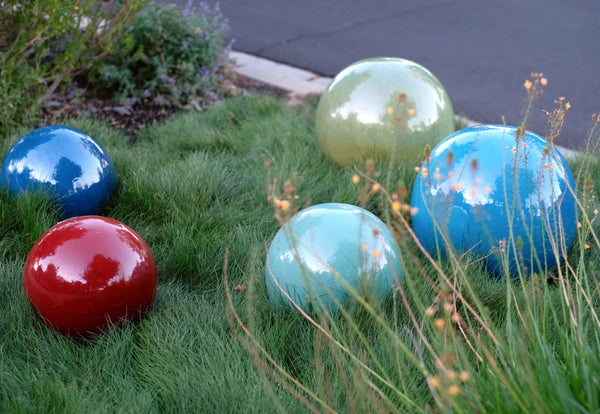 An image of five Decorative Yard Balls patio decor from Creative Living in various sizes sitting in the grass.