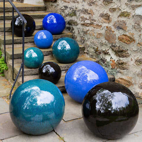 An image of nine Glazed Spheres patio decor from Creative Living in various sizes sitting on stone steps.