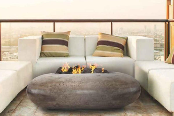 An image of the Pebble modern fire pit from Creative Living in front of an outdoor sofa.