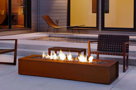 An image of the Cor-Ten Steel Robata Linear modern fire pit from Creative Living in front of a bench.