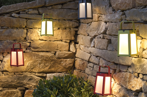 An image of five different colored Tinka Aluminum solar lanterns from Creative Living hanging on a rock wall.