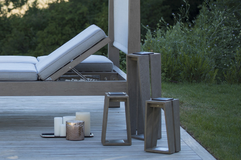 An image of three grey Skaal solar lanterns from Creative Living next to a lounge chair.