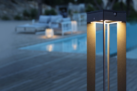 A close-up image of the Faro solar lantern from Creative Living with a pool in the background.