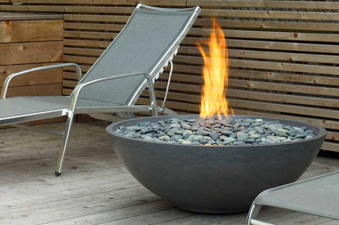 An image of the Miso modern fire pit from Creative Living next to a lounge chair.
