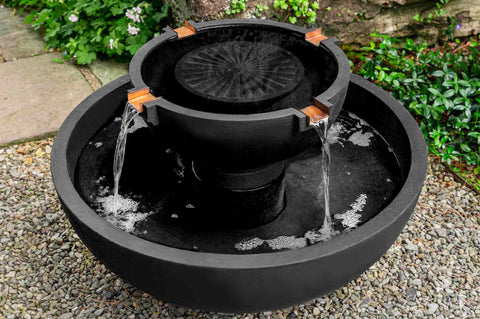 An image of the Del Rey modern fountain from Creative Living in black sitting in a garden.