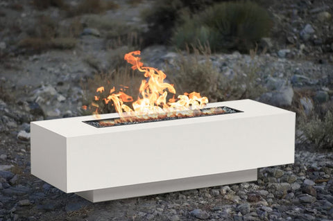 An image of the lit Ore Linear modern fire pit from Creative Living against a rocky background.