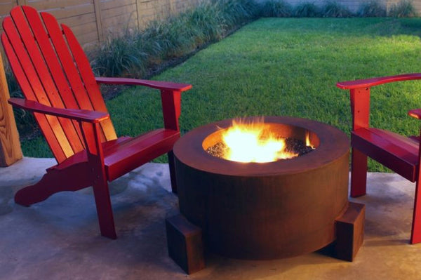 An image of the Cor-Ten Steel Round modern fire pit from Creative Living in a rust color between two red chairs.