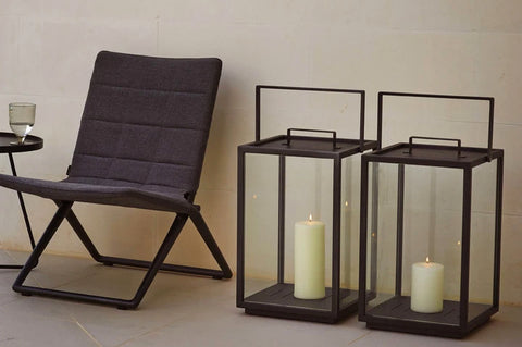 An image of two Lighthouse Aluminum Lanterns from Creative Living's collection of modern patio furniture sitting beside a chair.