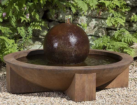 An image of the Low Zen Sphere modern fountain from Creative Living in brow sitting on a bed of pebbles.