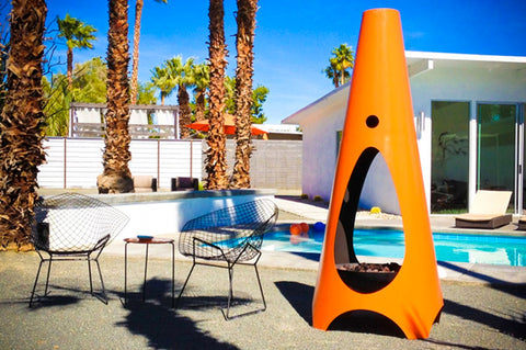 An image of the Cone modern fire pit from Creative Living in orange beside a pool.