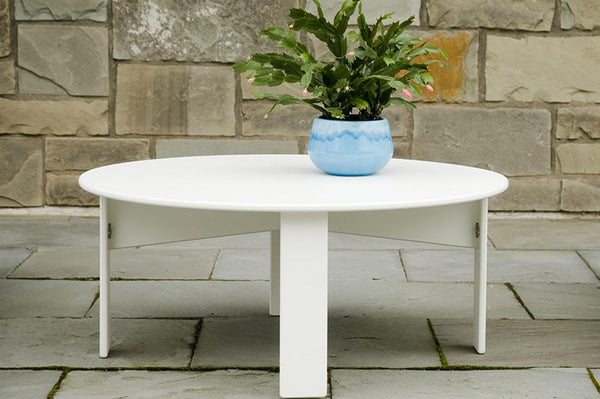 An image of the Lollygagger round outdoor table in white from Creative Living with a plant on top.