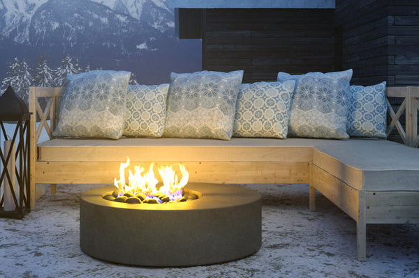An image of the lit Hestia Round Concrete modern fire pit from Creative Living.