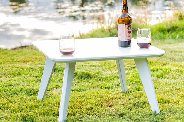An image of the square Satellite outdoor table in white from Creative Living with a bottle of wine and two wine glasses on top.