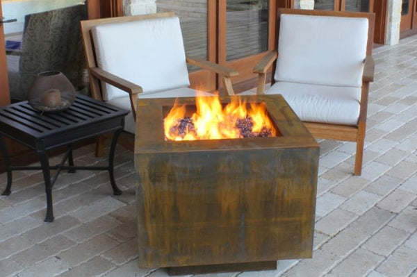 An image of the Cor-Ten Steel Square modern fire pit from Creative Living in front of two white chairs.