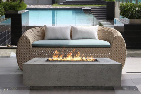 An image of the Creative Living Tavola modern fire pit in front of an outdoor love seat.