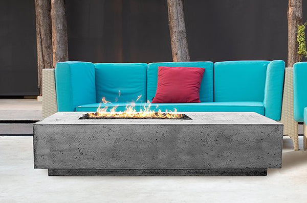 An image of the Tavola oblong modern fire pit from Creative Living in front of a blue couch.