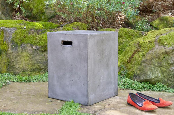 An image of the Urban Concrete Square End Table from Creative Living's collection of outdoor furniture sitting next to a pair of red shoes.