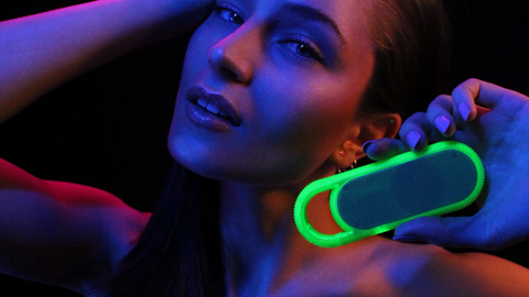 Girl listening to the Candywirez wireless/ portable neon speaker