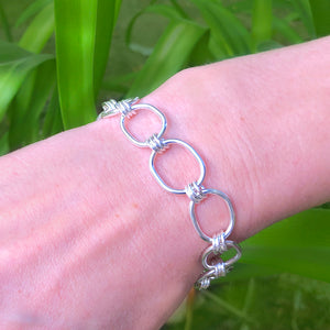 silver link bracelet on woman's wrist with green background