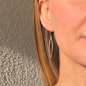 silver hammered leaf shaped hoops on ear wires on woman's ear
