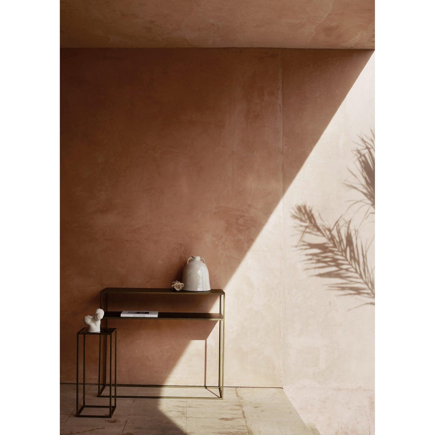 gold table resting against a pink wall with a matching side table