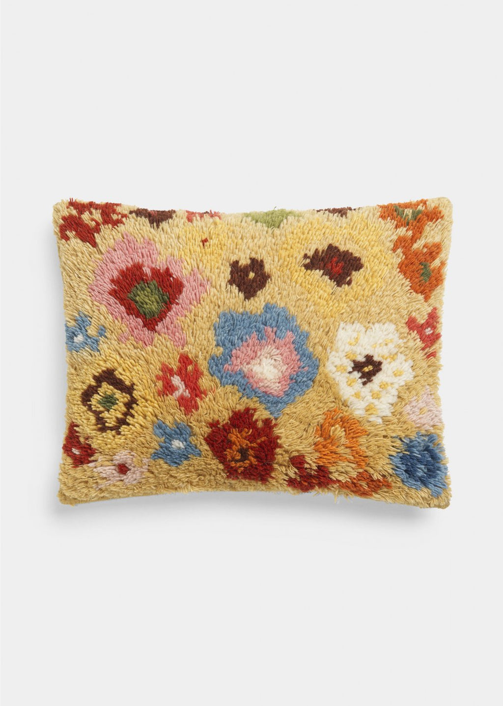 yellow wool pillow with brightly colored knitted flowers by designer aiayu