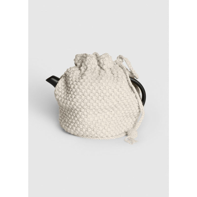 cream colored knitted tea cosy, on a black tea pot