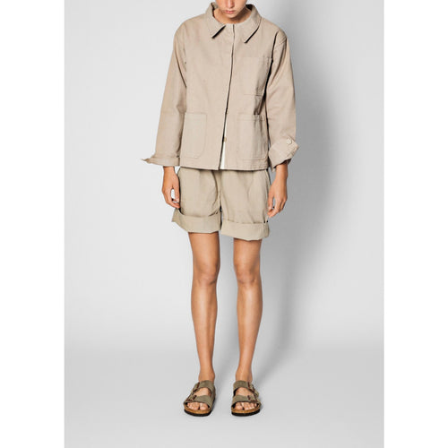 beige jacket paired with beige shorts and sandals