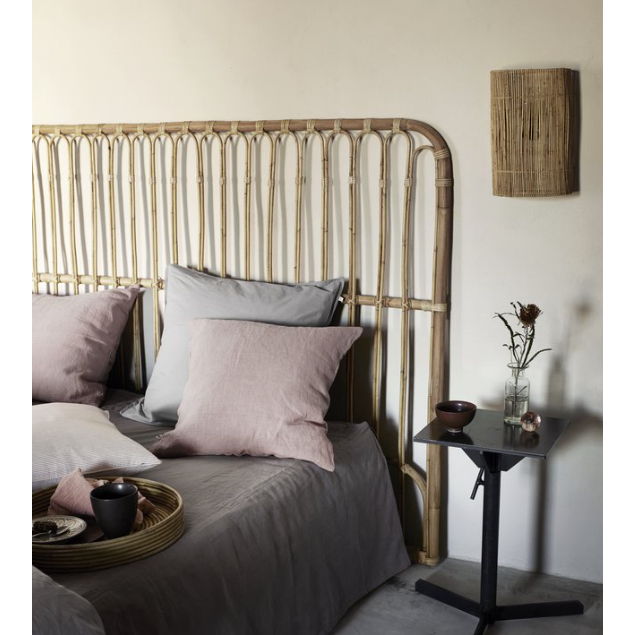 rattan headboard behind a bed with pillows and blankets