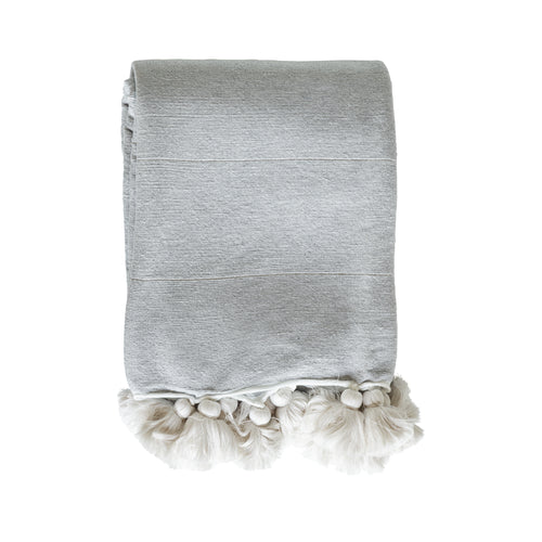 light grey blanket with cream color tassels by designer tine k