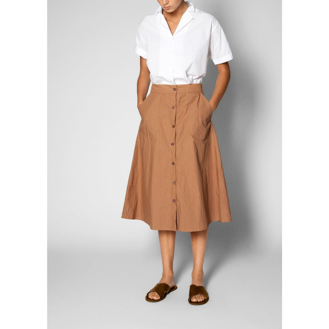 tabbaco colored a-line skirt with buttons down the front with a white shirt tucked into it