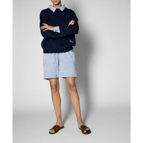 woman wearing blue organic cotton shorts with a blue button up under a navy sweater, with the collar peeking out